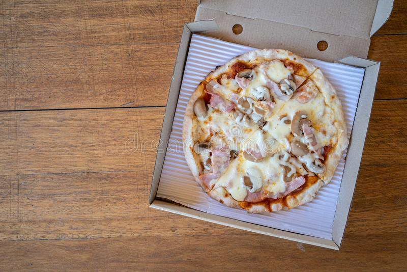 Homemade pizza with mushroom and ham in recycle paper box on wooden table royalty free stock image