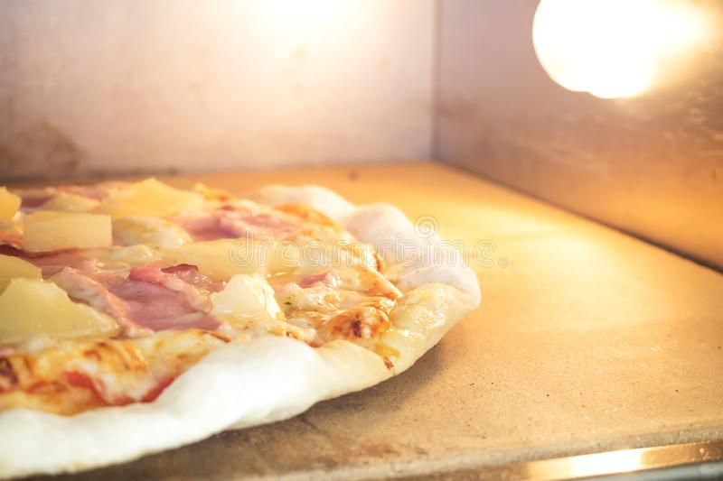 Homemade pizza in oven. Hawiian pizza. Favorite taste for lover. Closeup homemade pizza in oven. Hawiian pizza. Favorite taste for lover ham and pineapple. Junk royalty free stock photography