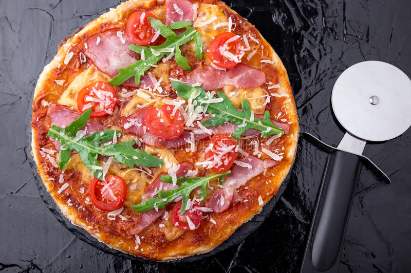 Homemade pizza with prosciutto, tomato, arugula on black slate board. Top view. royalty free stock photos