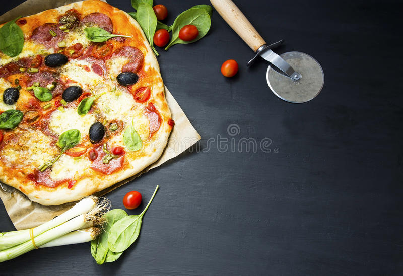 Homemade pizza with salami , cheese and olives, green spinach le royalty free stock photography