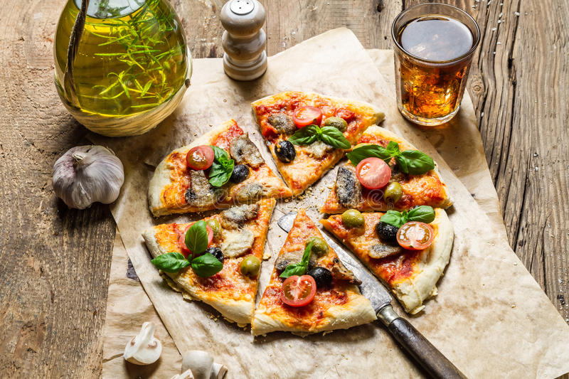Homemade pizza served on old wooden table stock image