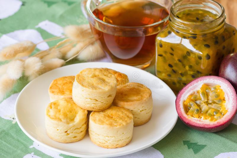 Homemade plain scones serve with homemade passion fruit jam. Scones is traditional English pastry for afternoon tea or coffee royalty free stock photo