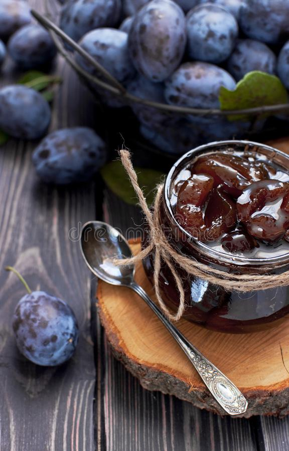 Homemade plum jam in a glass jar and fresh blue plums in a bowl on a dark rustic wooden background with copy space top view. Fruits, vitamins, food background stock photography