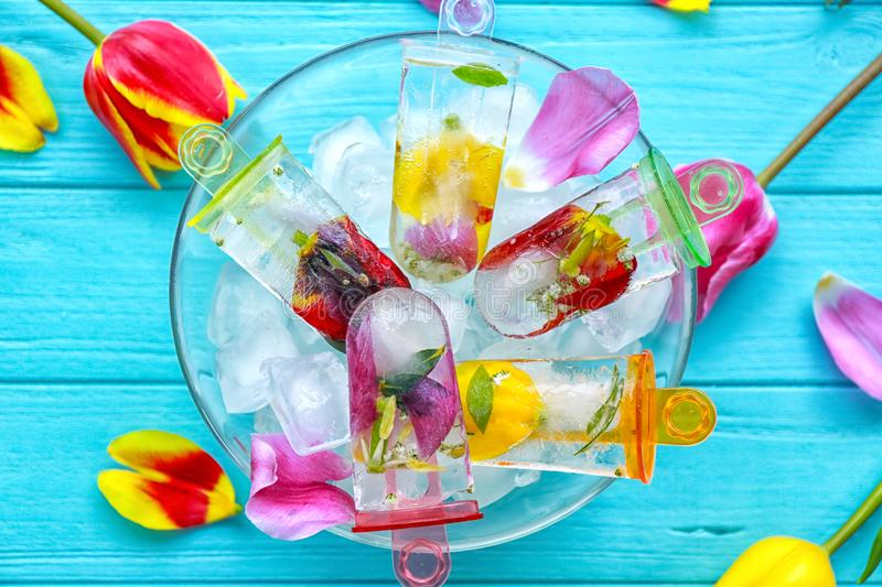 Homemade popsicles with flowers in glass bowl stock image