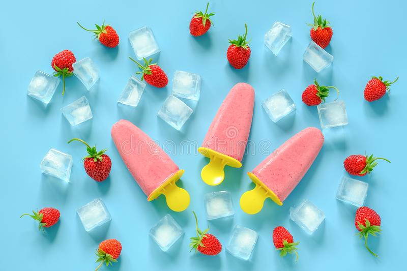 Homemade popsicles. Natural ice cream in bright plastic molds, strawberries and ice cubes on blue background. Top view Flat lay stock photography