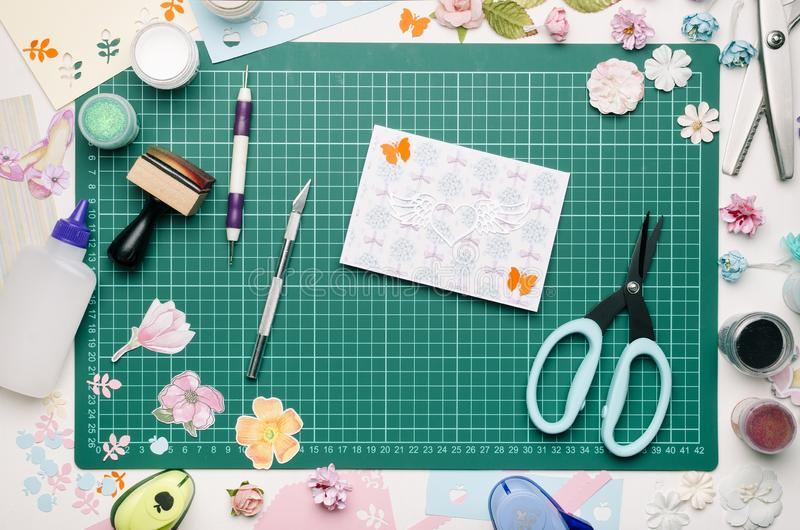 Homemade postcard on green cutting mat, tools and scrapbooking materials. No hands royalty free stock photography