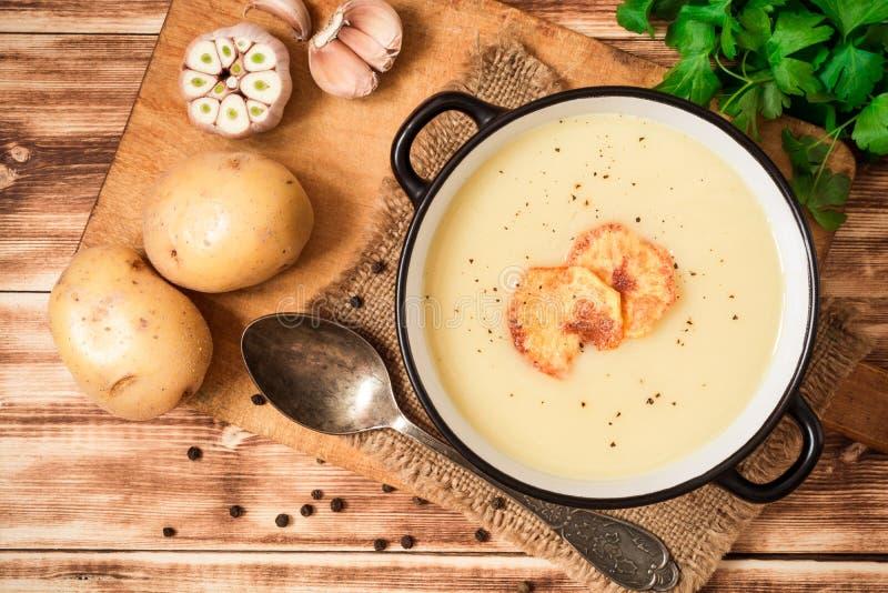Homemade potato cream soup with potato chips on wooden table royalty free stock photos