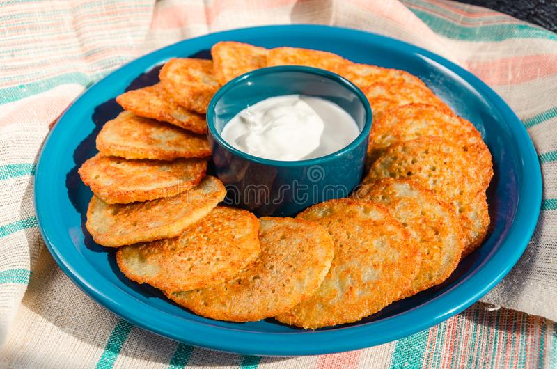Homemade potato pancakes, latkes, draniki, hash browns or fritters served with sour cream. Traditional Hanukkah treats royalty free stock photos