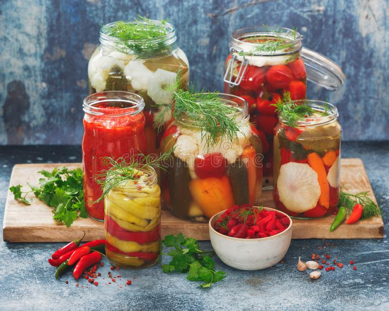 Homemade preserves and pickles of different vegetables in jars royalty free stock images