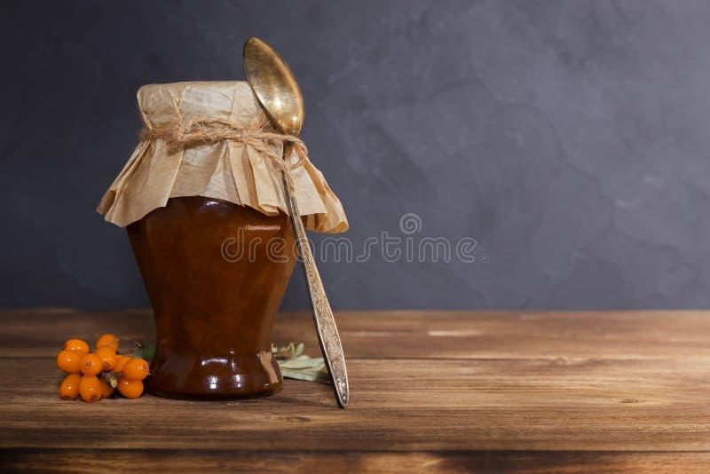 Homemade produktion av konserverande frukter och bär, sylt, pavidlo från mogna frukter av havs-bockthorn i en glasburk med en ske arkivfoto