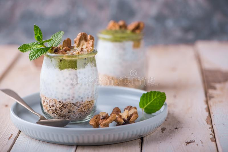Homemade pudding of Chia seeds and almond milk with cereals and puree of kiwi with walnuts and mint in glass jars. Vegan healthy royalty free stock image