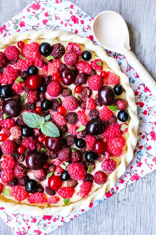 Homemade puff pastry sweet pizza pi with mascarpome cream cheese, fresh raspberry, strawberry, cherry, black currant decorated wit stock photo