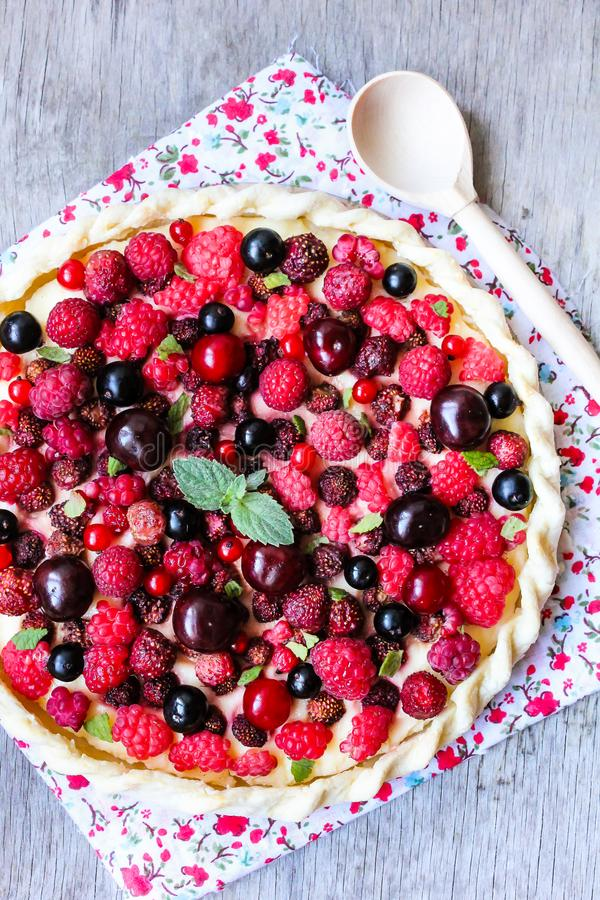 Homemade puff pastry sweet pizza pi with mascarpome cream cheese, fresh raspberry, strawberry, cherry, black currant decorated wit stock image