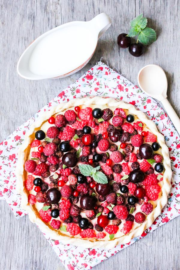 Homemade puff pastry sweet pizza pi with mascarpome cream cheese, fresh raspberry, strawberry, cherry, black currant decorated wit stock photography
