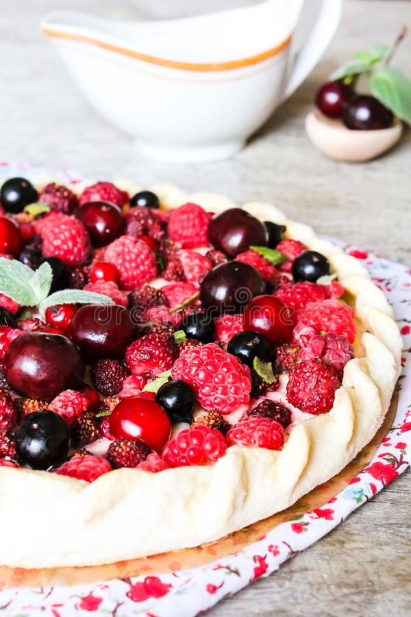 Homemade puff pastry sweet pizza pi with mascarpome cream cheese, fresh raspberry, strawberry, cherry, black currant decorated wit royalty free stock photos