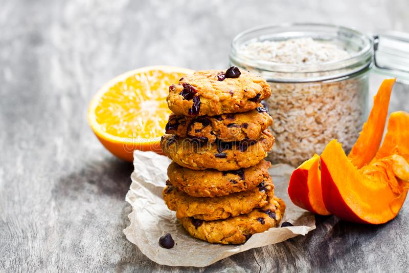 Homemade pumpkin and orange cookies on rustic wooden background stock photography