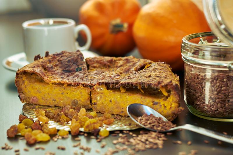 Homemade pumpkin pie with raisins, linseeds and flax flour on wooden table with cup of coffee and pumpkins stock images