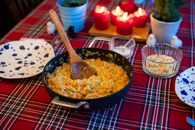 Pumpkin risotto served with pan on dining table royalty free stock photography