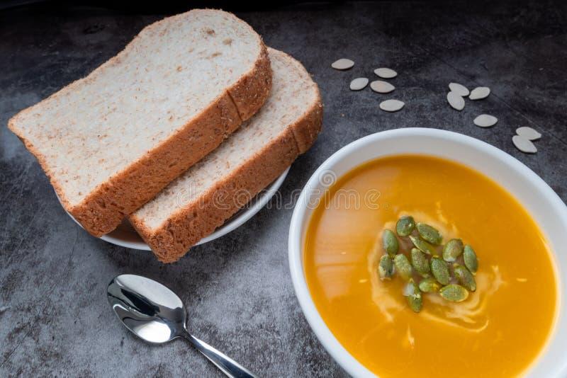 Homemade Pumpkin-soppa i en skål med helvetebröd och pumpafrön, toppvy, kopieringsutrymme Säsongsbunden höstmat veganmat royaltyfria foton