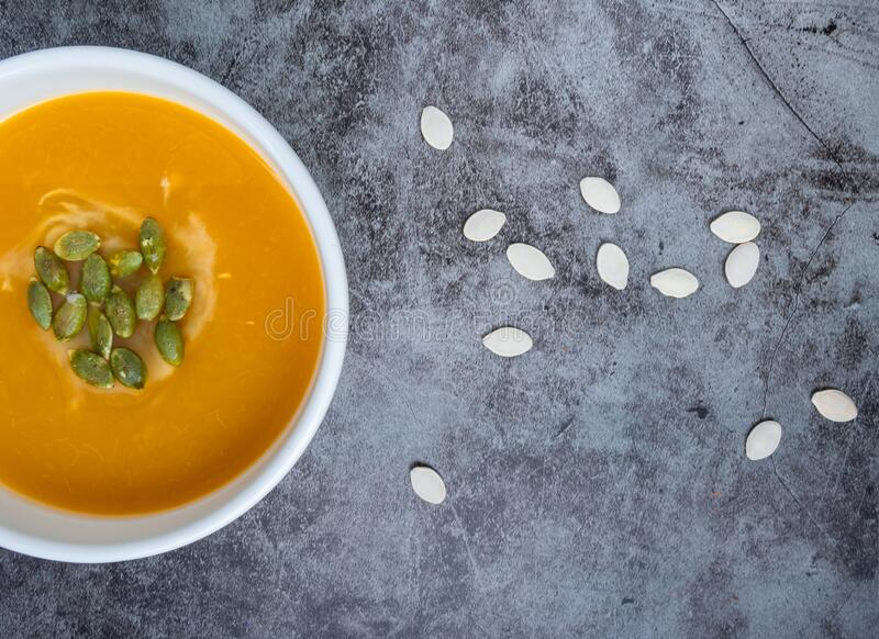 Homemade Pumpkin-soppa i en skål med pumpfrön, toppvy, kopieringsutrymme Säsongsbunden höstmat veganmat arkivfoto