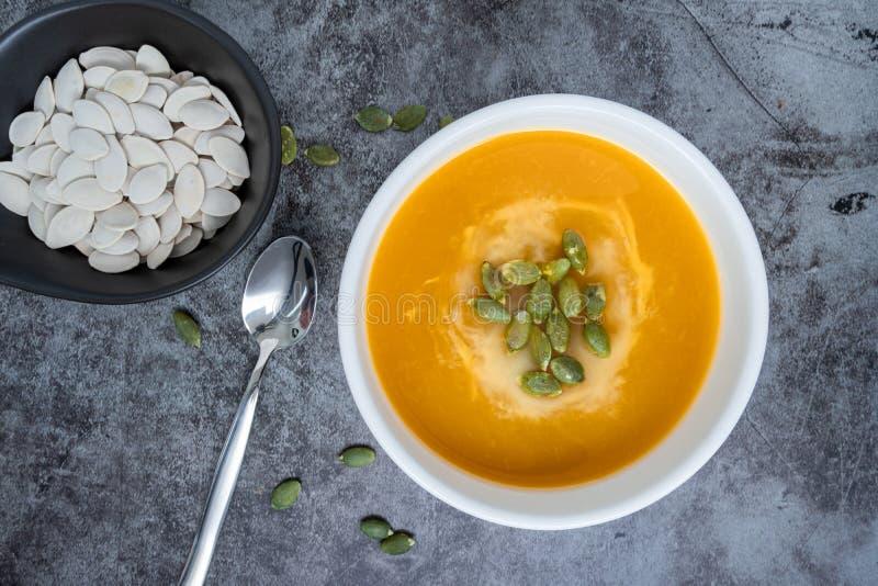 Homemade Pumpkin-soppa i en skål med pumpfrön, toppvy, kopieringsutrymme Säsongsbunden höstmat veganmat arkivfoton