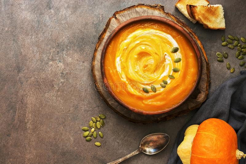 Homemade pumpkin soup in a clay plate served with sour cream, seeds and toast. Dark brown rustic background. Top view, copy space stock photography