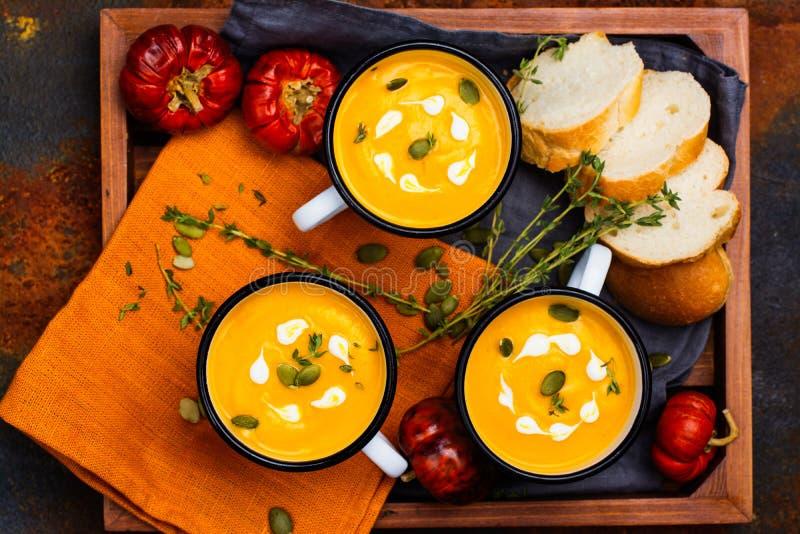 Homemade pumpkin soup in retro enamel mugs stock photo