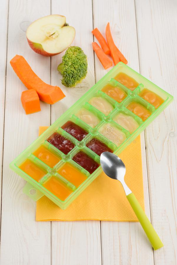 Homemade puree in freezer container. Fruits and veggies on wooden table. Storage of precooked baby food royalty free stock photo