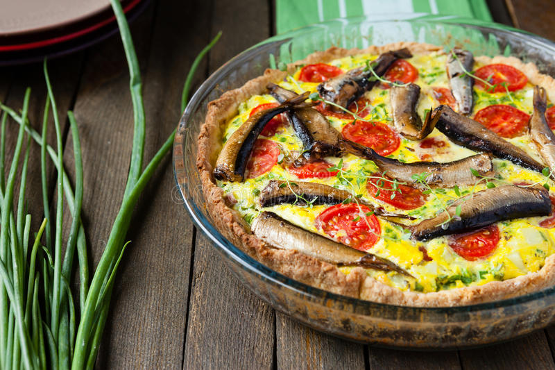 Homemade quiche with vegetables and fish, sprats stock photography