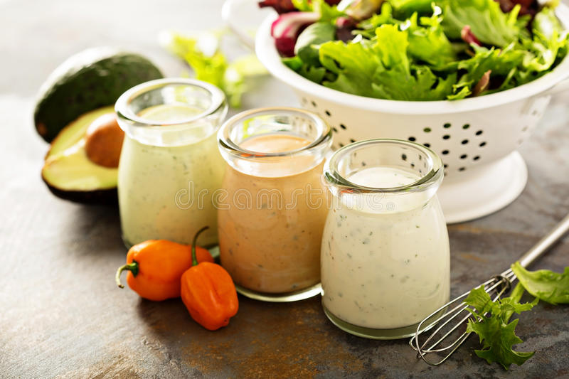 Homemade ranch dressing variety in small jars. With herbs, avocado and hot pepper stock photos