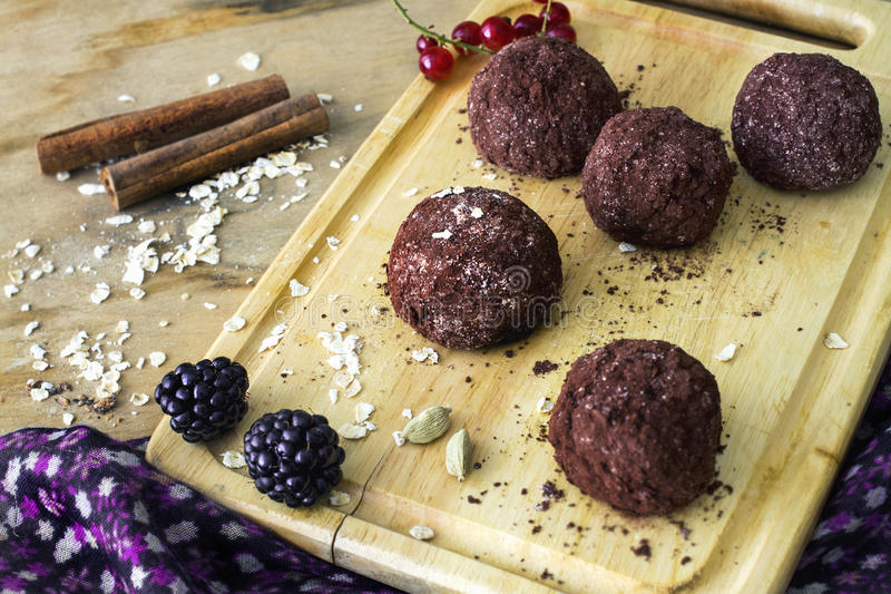 Homemade raw healthy vegan chocolate truffles with muesli. On wooden background stock images