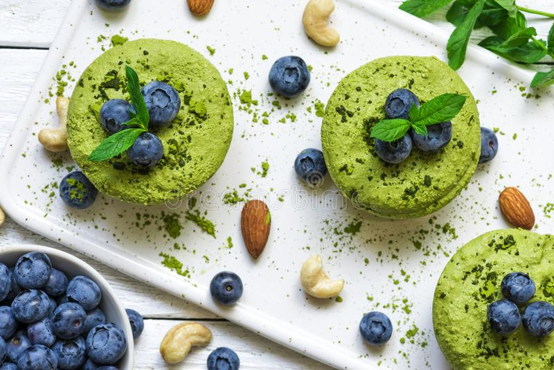 Homemade raw matcha powder cakes with fresh berries, mint, nuts. healthy vegan food concept. Top view stock images