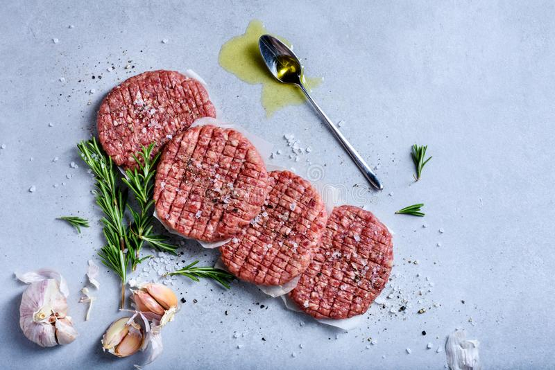 Homemade raw minced beef steak burgers with spices royalty free stock photo