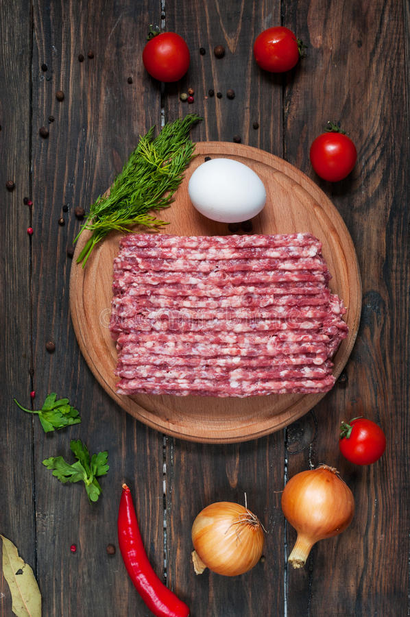 Homemade raw minced meat with egg and herbs closeup, top view royalty free stock photography