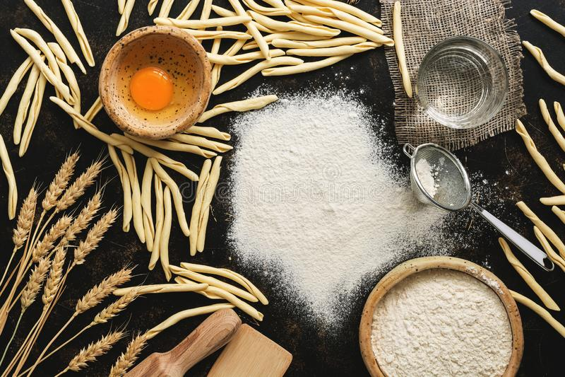 Homemade raw pasta and ingredients for cooking pasta, flour, egg, water. View from above royalty free stock photos
