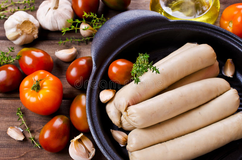 Homemade raw sausages. With vegetables on a wooden background. Selective focus royalty free stock photo