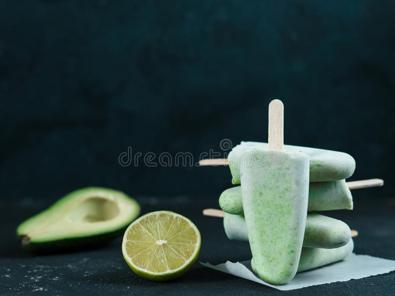 Avocado lime popsicle, copy space. Homemade raw vegan avocado lime popsicle. Sugar-free, non-dairy green ice cream on black textured background. Copy space stock photography