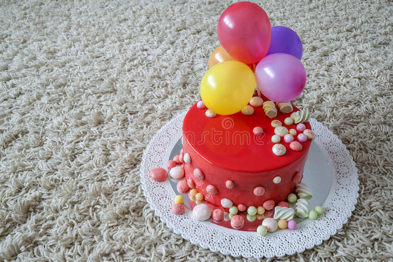 Homemade red birthday cake with air baloons.  stock photo