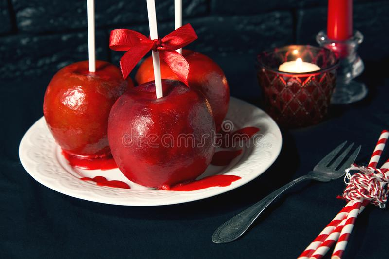 Homemade red caramel coating apples on a sticks for Christmas and New Year royalty free stock images