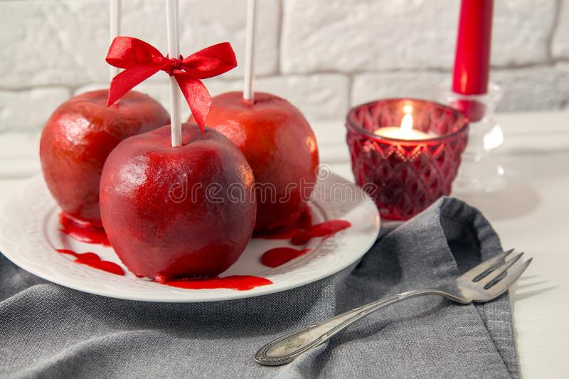 Homemade red caramel coating apples on a sticks for Christmas and New Year stock images