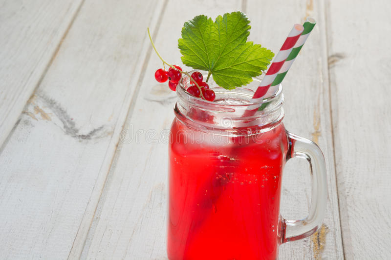 Homemade red currant lemonade in a mason jar and garnish of berry branch on ligth wooden table. Homemade red currant lemonade in a mason jar with decor of berry royalty free stock photos