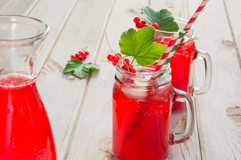 Homemade red currant lemonade in a mason jar and garnish of berry branch on ligth wooden table. Homemade red currant lemonade in a mason jar with decor of berry stock photography