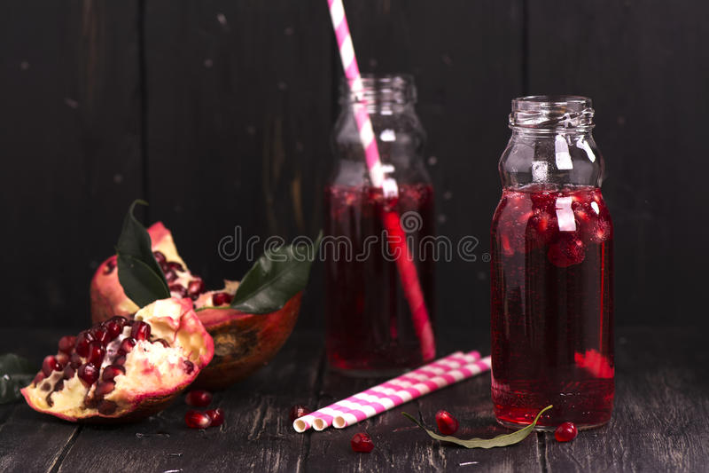 Homemade red pomegranate lemonade in small glass bottles royalty free stock photo
