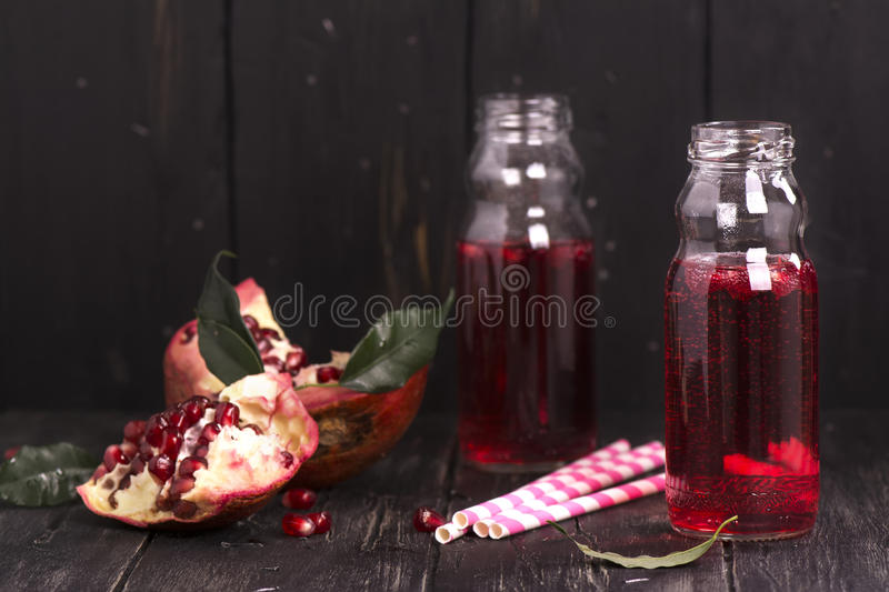 Homemade red pomegranate lemonade in small glass bottles royalty free stock photos
