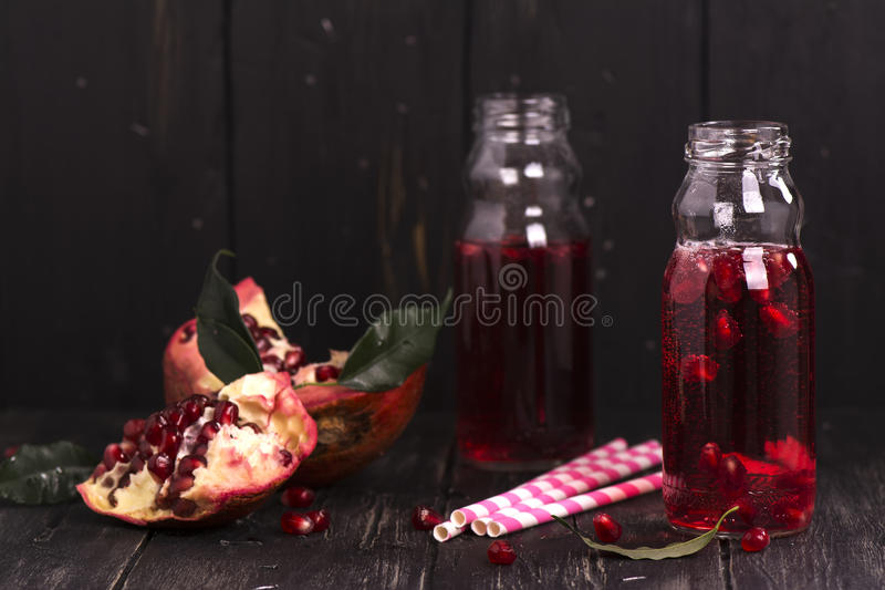 Homemade red pomegranate lemonade in small glass bottles stock photo