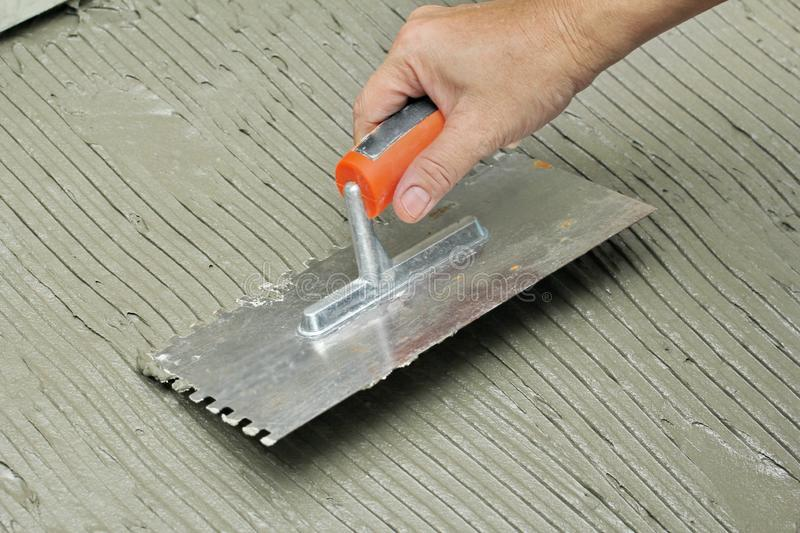 Homemade Replacing floor tiles , Fill tile adhesive plaster in full at old  area to and set surface level by using broad hell stock images