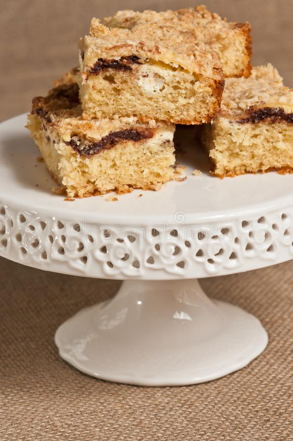 Homemade ricotta and chocolate coffee cake. Four squares of homemade ricotta cheese and chocolate coffee cake stacked on a white, round, pedestaled dish on a stock image