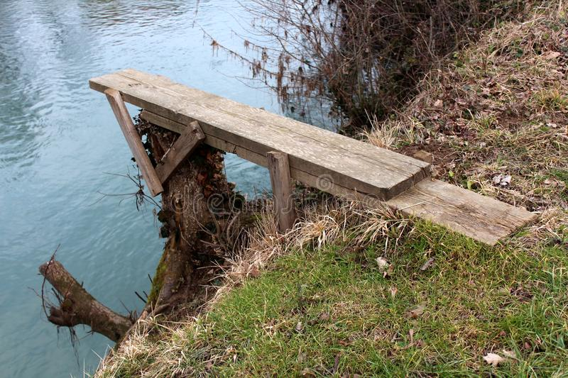 Homemade river diving board mounted on tree stump. Homemade river diving board made from planks mounted on tree stump on river bank covered with uncut grass and royalty free stock photos