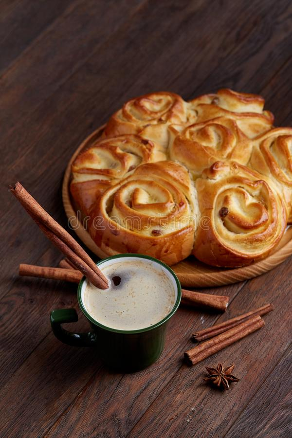 Homemade rose bread, cup of coffee, anise and cinnamon on vintage background, close-up, selective focus stock photography