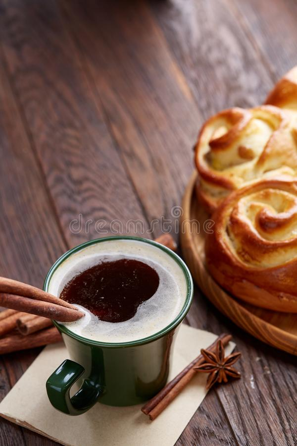 Homemade rose bread, cup of coffee, anise and cinnamon on vintage background, close-up, selective focus stock photo